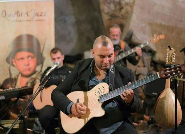 Mario Romano suona la chitarra con i Quartieri Jazz