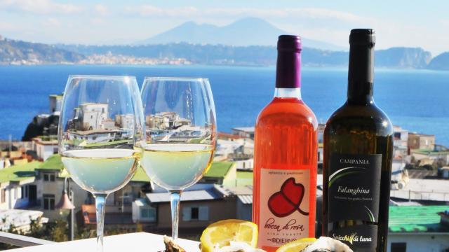 Calici di vino con il golfo di Napoli sullo sfondo